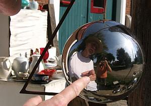 Dicke Glaskugeln vor einem Laden mit Nutzkunst spiegeln die Betrachter wider.